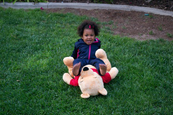 Girl playing with stuffed Winnie the Pooh