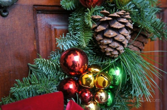 Pine cones, ornaments, bells on fresh Christmas wreath