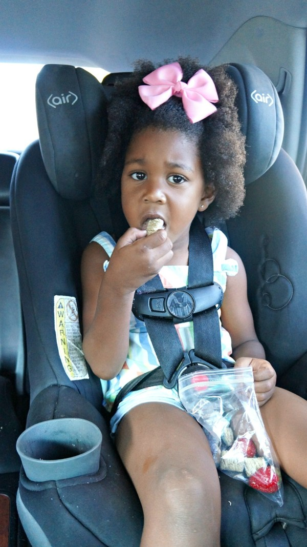 Toddler eating breakfast in the car