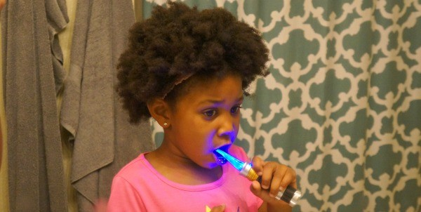 Girl brushing her teeth with Firefly® Light up Toothbrush