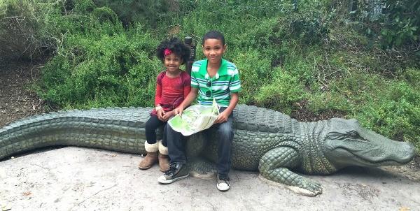 KIND at the Los Angeles Zoo, kids sitting on a crocodile