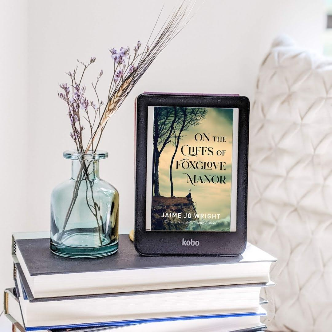 On the Cliffs of Foxglove Manor ebook set beside flower, on white background