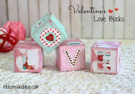 On a cream tablecloth wooden blocks are decorated with patters and the letters L, O, V and E