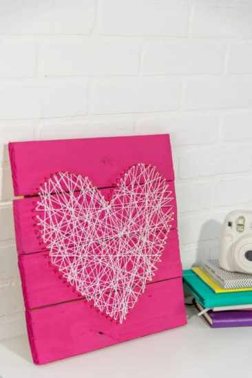 Resting up against a cream wall is a pink wooden board. On the front of it is a heart made from string and nails in white.