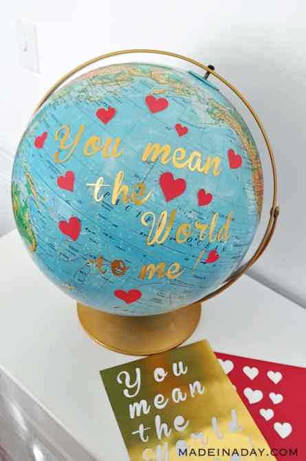 """A globe with a gold stand sits on a white table. The globe is covered in red hearts and the tgold text """"You mean the world to me"""""""