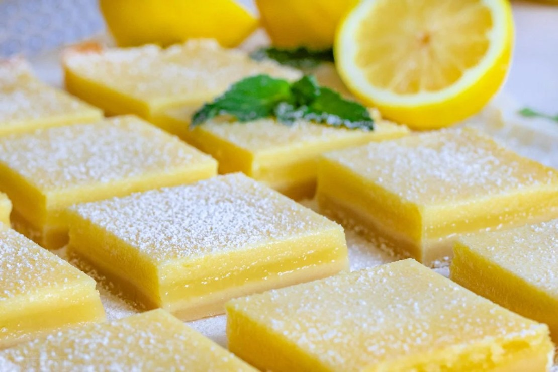 entire recipe of lemon bars cut up on white parchment with fresh lemons in background.