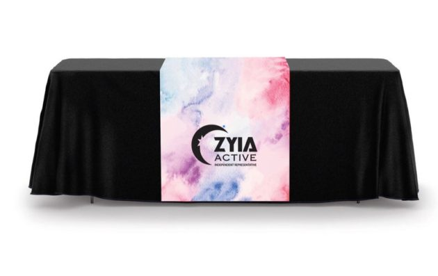 Photo of black table cloth on a table with Zyia Active branded table runner on top. Runner has a variety of colors on it including pink, blue, and purple.