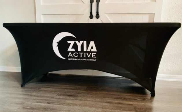 Photo of fitted black table cover on a table in a room with Zyia Active logo printed in white on it.