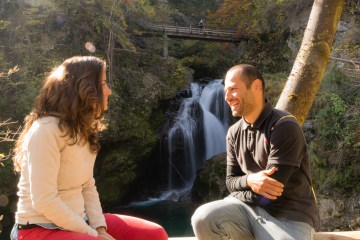 Tiago and Fernanda from Monday Feelings in front of a waterfall in Bled gorge