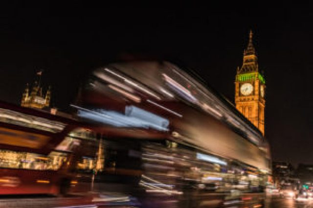 The Big Ben and London buses at night