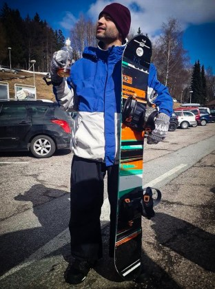 Tiago holding a snowboard and a bottle