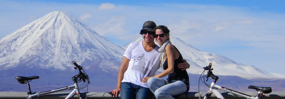 Tiago and Fernanda from Monday Feelings cycling in Atacama, Chile, with snowed peak mountains in the back