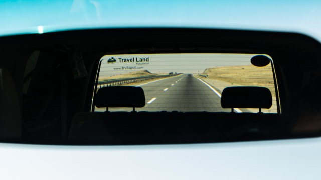 logo of Travel Land on the rear window of the car over looking an infinity motorway