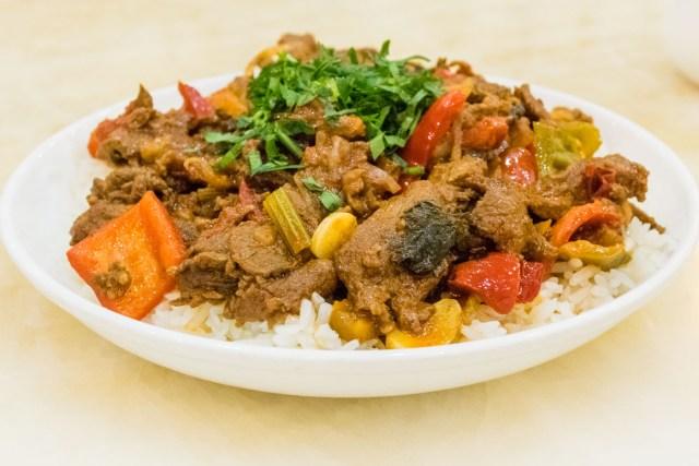 Prato tradicional do quirguistão com carne, vegetais e arroz
