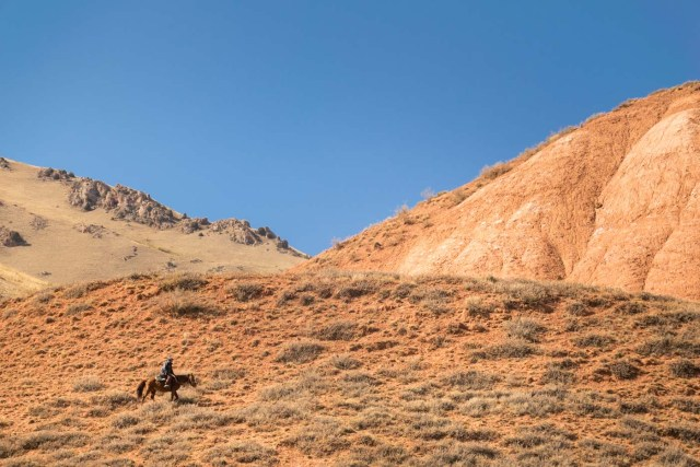 man on horse in the mountain of kyrgyzstan