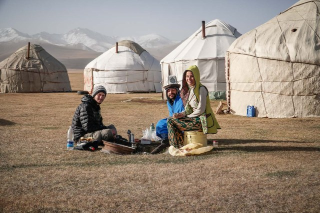 Tiago, Fernanda and a man building a fire in Kyrgyzstan