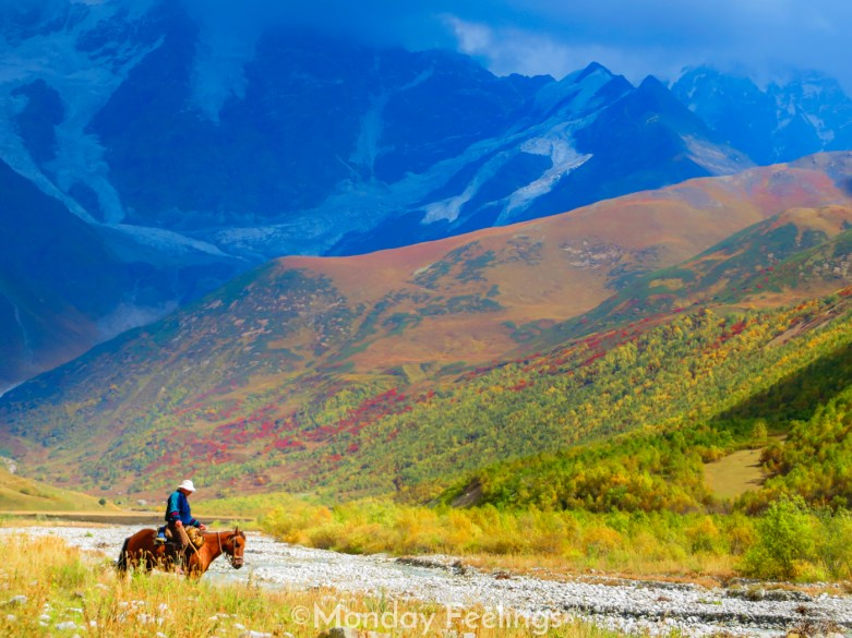 A man on a horse in an open field in a remote village