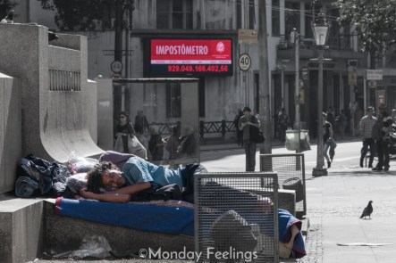 A homeless sleeping and a sign of how much tax has been collected in Sao Paulo, Brazil
