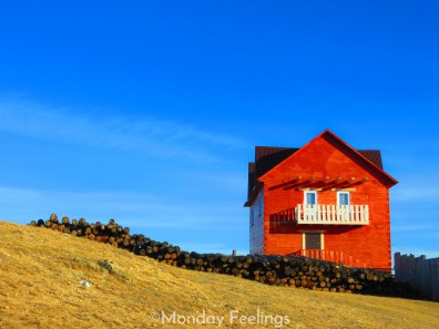 A wooden red house with a blue sky