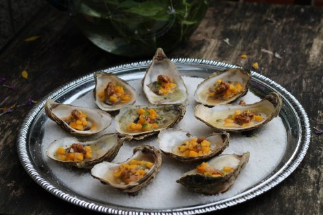 Grilled oysters with mango pico de gallo, and horseradish chili