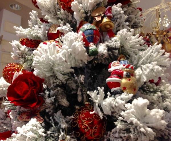 albero di natale innevato con balocchi e palline rosse