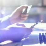 Closeup photo businessman working with generic design smartphone. Online payments, banking, hands keyboard. Blurred background, film effect.