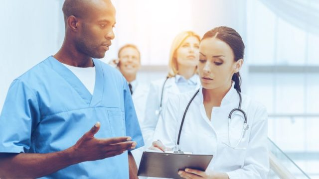 Medical Assistant With Doctor Discussing Patient Notes