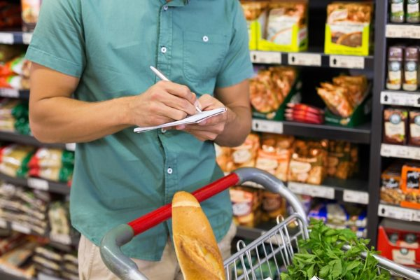 Man checking off items on shopping list
