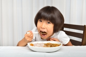 Little Asian girl eating curry