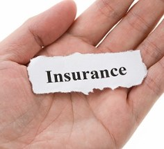 handing holding a piece of paper which says insurance