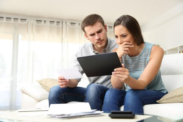 Worried couple looking at a tablet