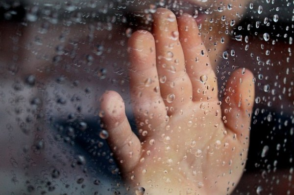 Child with hand pressed against a wet window