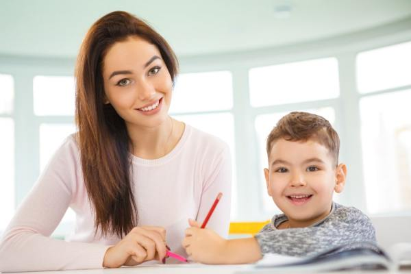 Young female tutor teaching young boy