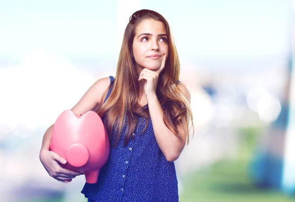Woman holding piggy bank and looking thoughtful