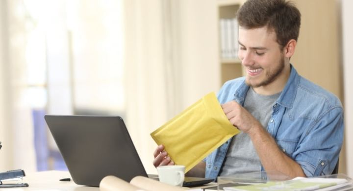 Man placing items in padded envelope