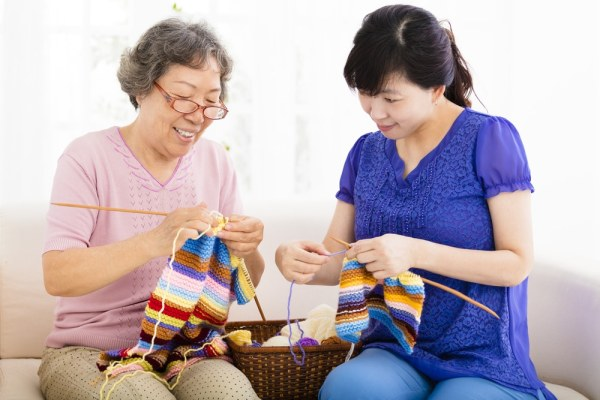 Older woman teaching younger woman to knit