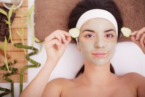 Woman wearing mud mask holding cucumber slices up to her eyes