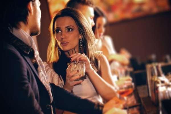 Woman talking to stranger at bar