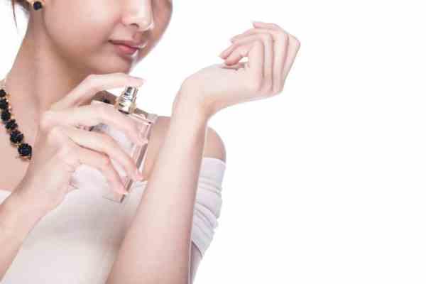 Woman spraying perfume on wrist