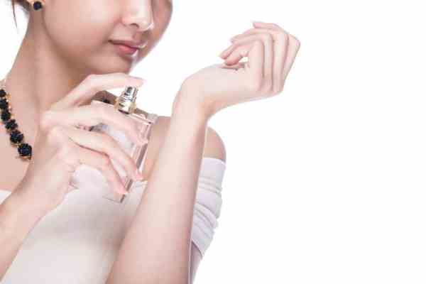 Woman spraying perfume on wrist