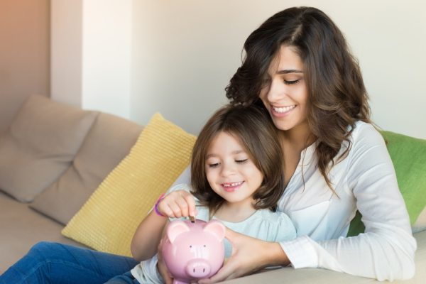 Mother and young daughter putting coin in piggy bank