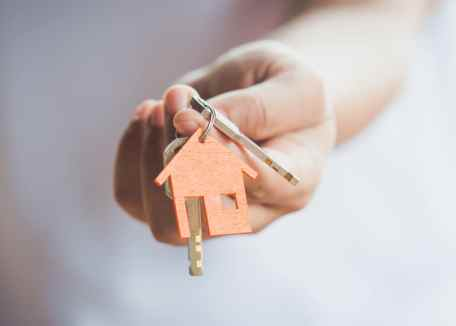 Hand holding keys with house keyring