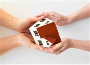 2 sets of hands holding a model house