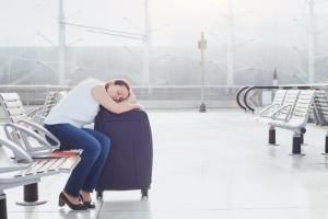 Woman sleeping on her suitcase at the Airport