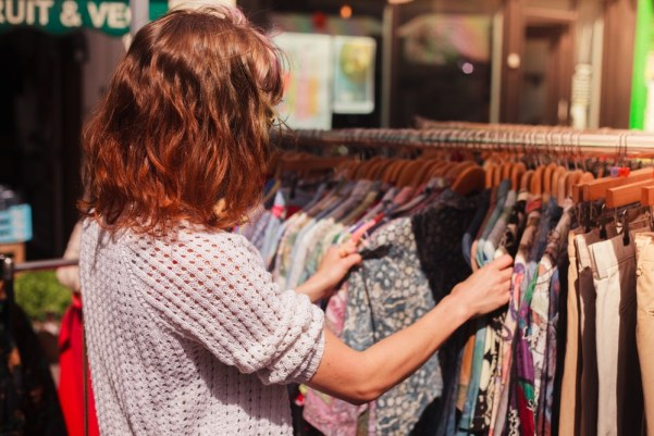 Girl looking through clothes on a rail in a vintage/charity shop