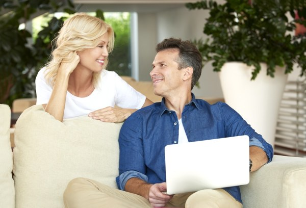 Happy middle aged couple using laptop