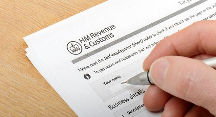 Person filling in HMRC tax forms