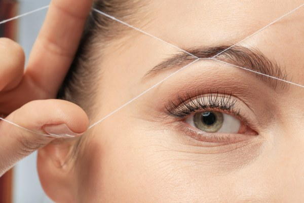 Woman threading her eyebrows