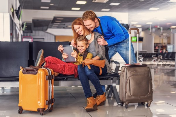 Family using tablet in departure lounge