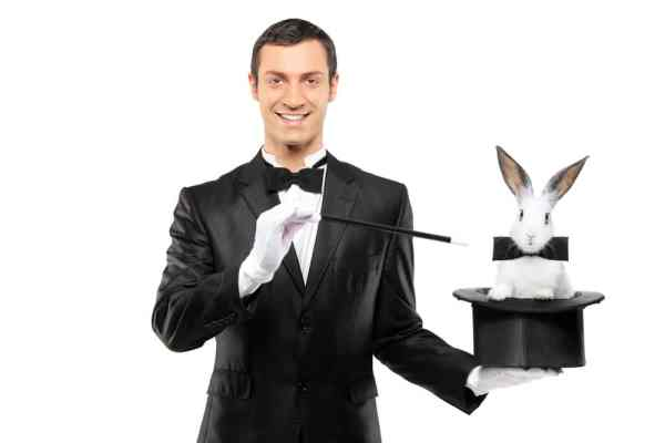 Male magician holding wand, top hat and rabbit